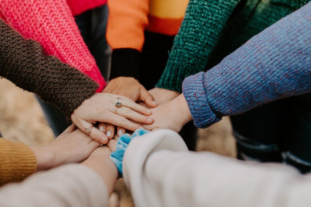 aufeinander gelegte Hände im Kreis